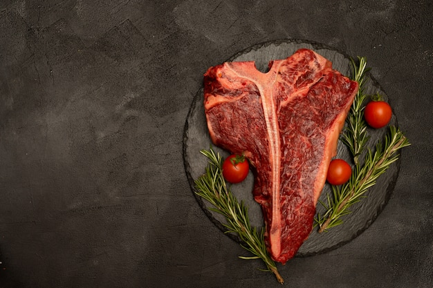 T-bone or porterhouse  with tomatoes and rosemary on a black background.
