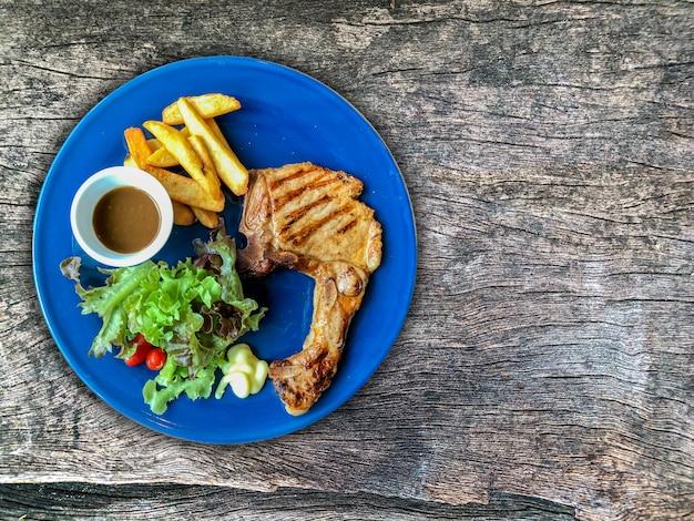 T bone steak on dish and wood