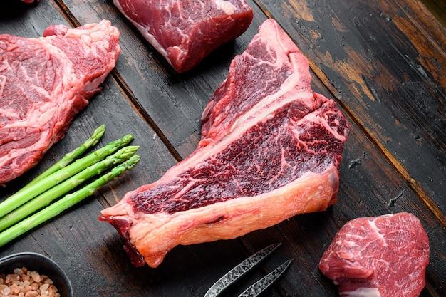 Стейк на косточке. органическое сырое мясо говядины tbon под мрамор, на фоне старого темного деревянного стола