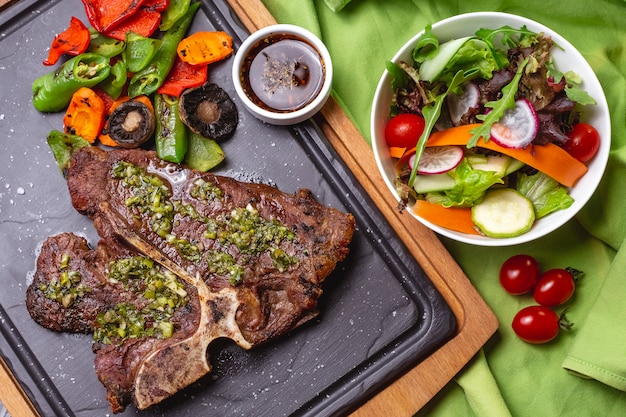 T-bone steak with greens bell pepper tomato carrot mushroom with green salad in bowl top view