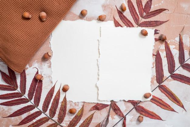 素朴な木製の背景に紅葉のフレーム。美しい黄色の紅葉の境界線。メモの破れた紙のトレンド。季節の収穫t、秋のカード。フラット横たわっていた、トップビュー。 copyspace。