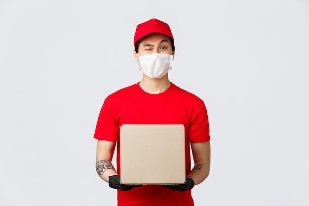 赤い帽子とtシャツのフレンドリーなアジアの配達人、クライアントと従業員の安全のための保護手袋と医療用マスクの着用、covid-19検疫中の家の配達、ホールドインボックスパッケージ