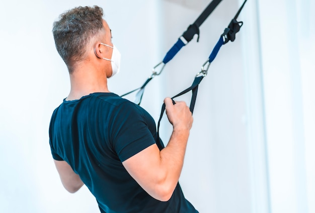 マスクと腕の練習をしている黒いtシャツの患者。 covid-19パンデミックにおける理学療法士のセキュリティ対策を再開。オステオパシー、治療用キロマッサージ