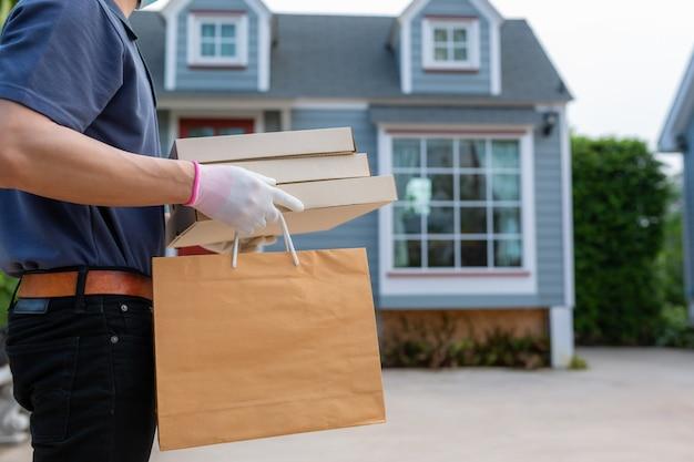 ブルーキャップtシャツユニフォームマスクグローブのアジアの配達人従業員は、持ち帰り用の食品のクラフトペーパーパケットを保持します。コンセプトサービス検疫パンデミックコロナウイルスウイルス[covid-19]