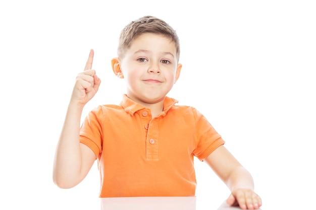 明るいオレンジ色のポロtシャツを着たかわいい学齢期の少年が、親指を上にしてテーブルに座っています。白い背景の上のisolirvoan。