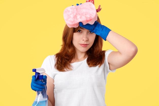 衛生とクリーニングのコンセプト。ゴム手袋と白いtシャツで疲れたonworked女性、家事をした後疲労を感じ、額をこすり、クレンザーとスポンジを保持し、黄色の壁に分離