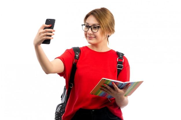 コピーブックと黒のスマートフォンを保持している黒いバッグを身に着けている赤いtシャツの正面の若い女子学生、selfieを白