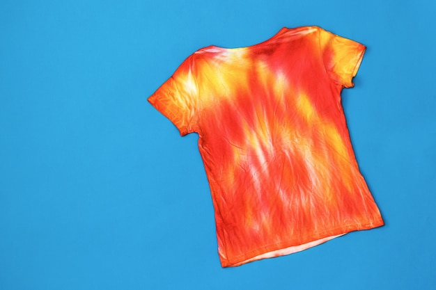 T-shirt decorated in tie dye style in yellow and red colors on a blue surface