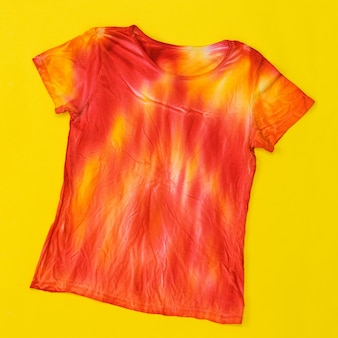 T-shirt decorated in tie dye style in yellow and red colors. flat lay. staining fabric in tie dye style. flat lay.