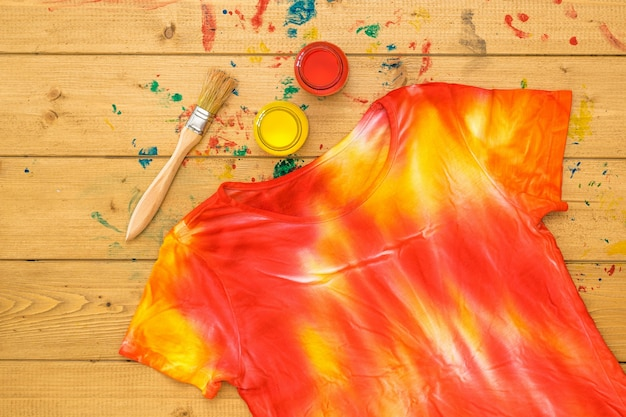 T-shirt decorated in tie dye style in yellow and red colors on a wooden table. staining fabric in tie dye style. flat lay.