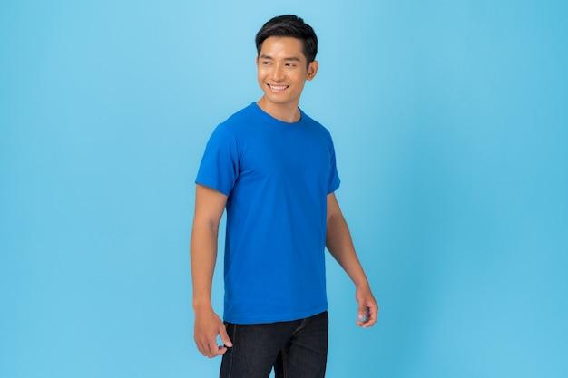 Дизайн футболки, молодой человек в синей футболке, изолированные на синем
