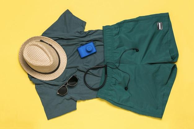 노란색 표면에 헤드폰 t- 셔츠, 모자 및 반바지. 평평하다. 여름 방학 및 여행.