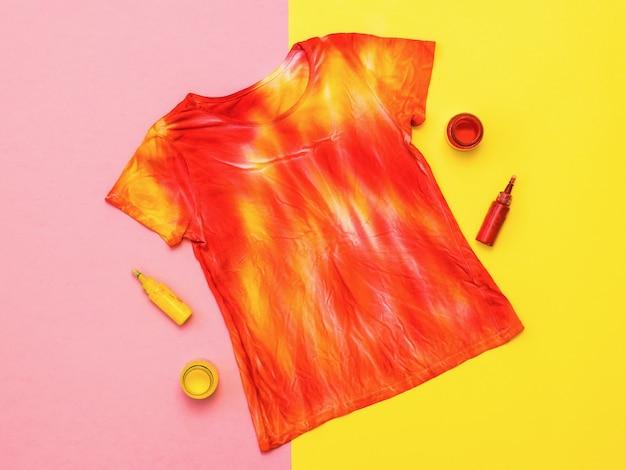 タイダイのスタイルのtシャツと黄色と赤のペンキの瓶。絞り染め風の染み布。フラットレイ。