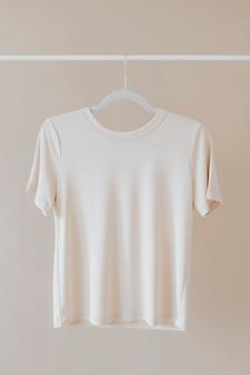 衣類ラックにぶら下がっているtシャツのモックアップ