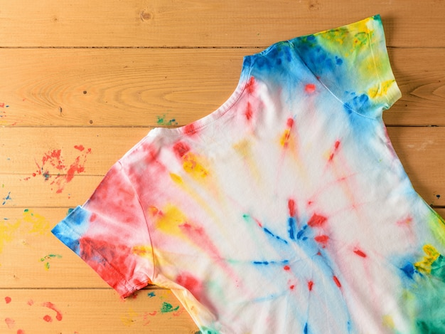 T-shirt painted in the style of tie dye on a wooden desktop