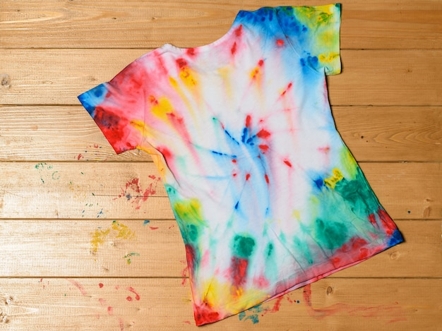 T-shirt painted in tie dye style on a brown table. flat lay. the view from the top.