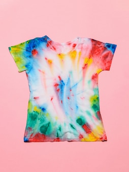 T-shirt painted in tie dye style on a pink background