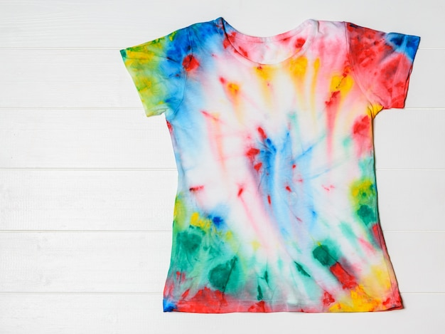 T-shirt painted in tie dye style on a white table