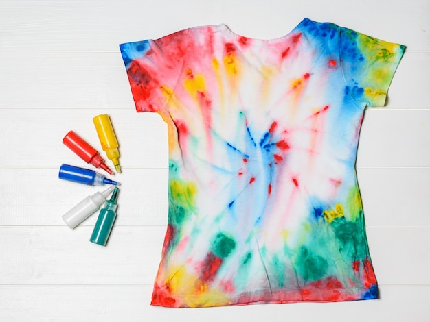 T-shirt painted in tie dye style with colors on a white wooden table. flat lay.