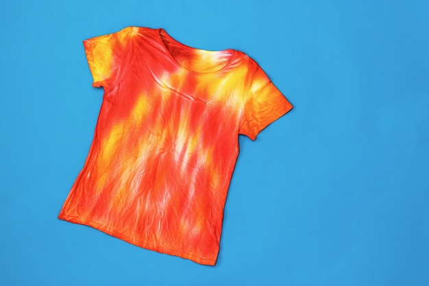T-shirt in red and yellow in the style of tie dye on a dark blue