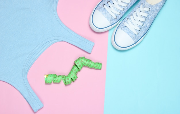 T-shirt, ruler, sneakers on pastel. flat lay style.