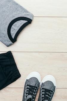 木製の背景にズボンと靴を持つtシャツ