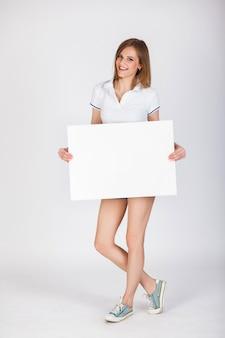サインボードデニムのショートパンツとt  -  shirthの美しい若い女の子