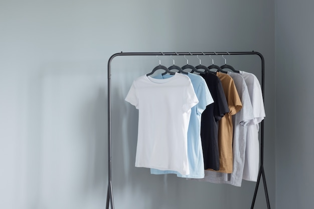 灰色の壁に黒いハンガーの中間色のtシャツ