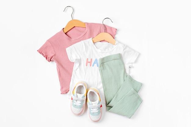 옷걸이와 운동화에 티셔츠. 흰색 바탕에 봄, 가을, 여름을 위한 아기 옷과 액세서리 세트. 패션 키즈 복장. 평평한 평지, 평면도