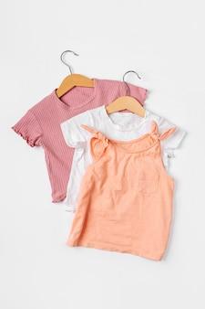 옷걸이에 티셔츠. 흰색 바탕에 봄, 가을, 여름을 위한 아기 옷과 액세서리 세트. 패션 키즈 복장. 평평한 평지, 평면도