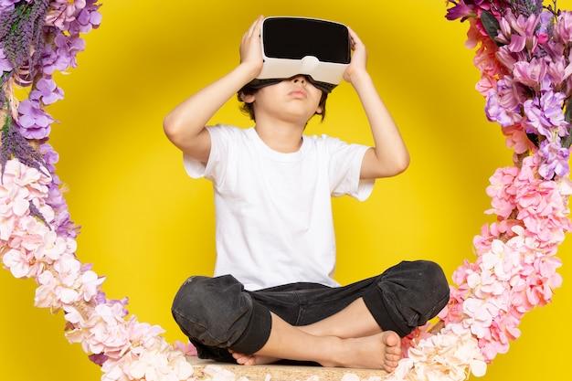 Вид спереди милый мальчик в белом t-shrit играет vr вокруг цветов на желтом пространстве