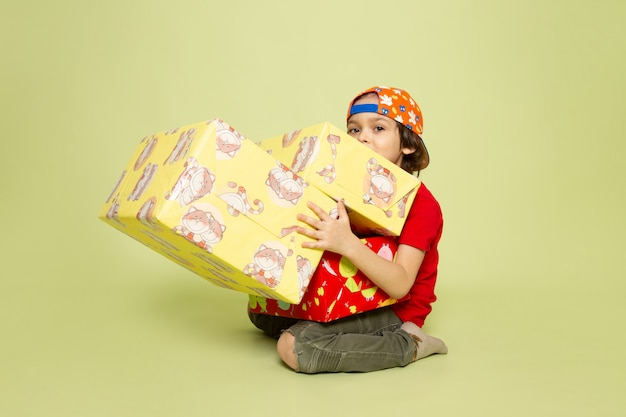 Вид спереди милый мальчик в красном t-shrit держит подарки на каменном цветном пространстве