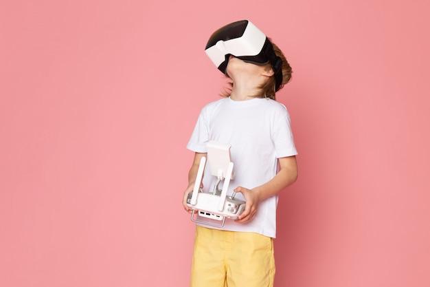 ピンクの床に白いtシャツと黄色のジーンズでvrを再生する白いtシャツで小さなかわいい子供を正面から見る