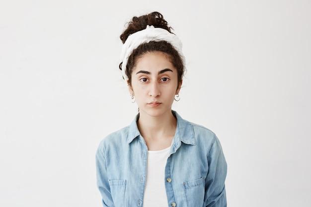 暗い髪の白いtシャツの上に黒い髪wearinf do-ragとデニムシャツで物思いにふける深刻な学生少女、白い空白の壁に対してポーズします。美しさと若さのコンセプト