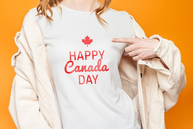白いtシャツの女の子はオレンジ色の背景に分離された言葉「ハッピーカナダデー」を指さします