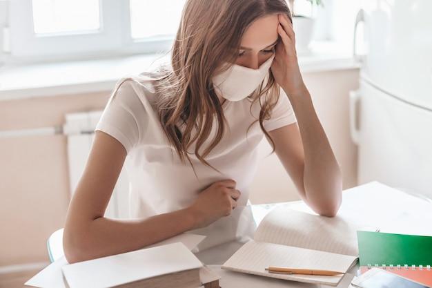 医療マスクと白いtシャツを着た物思いにふける若い女性が自宅のテーブルの部屋に座って、遠隔で働いています。自宅で勉強している学生の女の子、隔離隔離、ホームコンセプトを維持