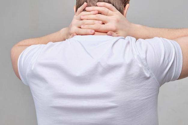 白いtシャツを着た男性が背骨の痛みのために首をマッサージします。
