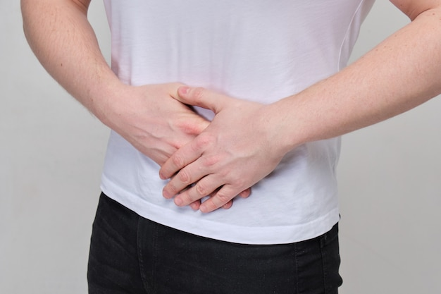 白いtシャツを着た男性は、膵臓、腸の激しい痛みのために胃をマッサージします。