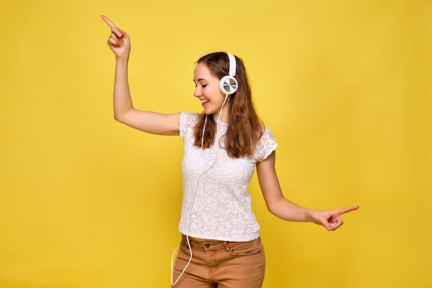 白いtシャツと黄色の背景に茶色のジーンズの女の子がリラックスして、白いヘッドフォンで音楽を聴いて踊ります。