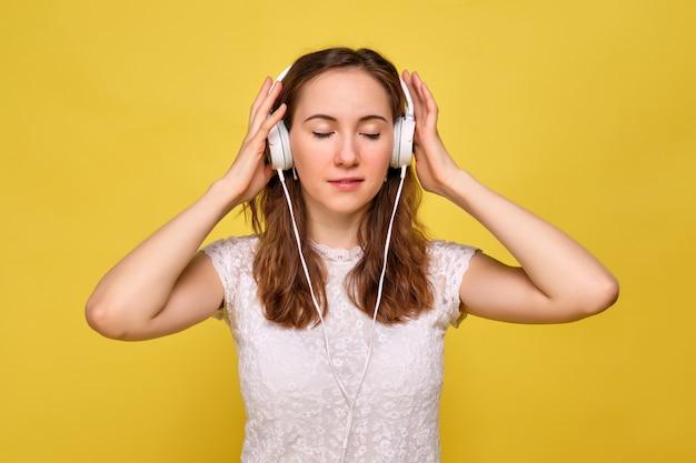 黄色の背景に白いtシャツと茶色のジーンズを着た女の子がリラックスして、白いヘッドフォンで音楽を注意深く聴いて楽しんでいます。