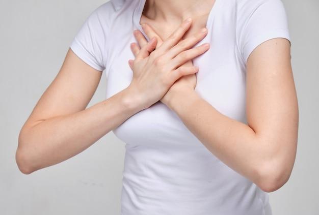 白いtシャツを着た女性は胸の痛みに苦しんでいます。呼吸困難。