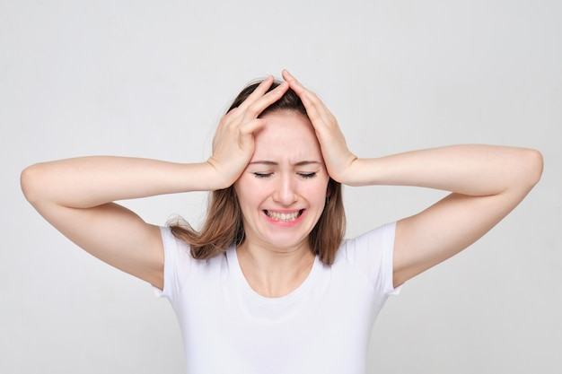 白いtシャツを着た女性が両手で頭を抱えています。ストレスと問題の概念。