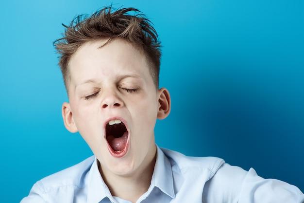 Tシャツを着た少年は疲れていて、眠りたいとあくびをしたい