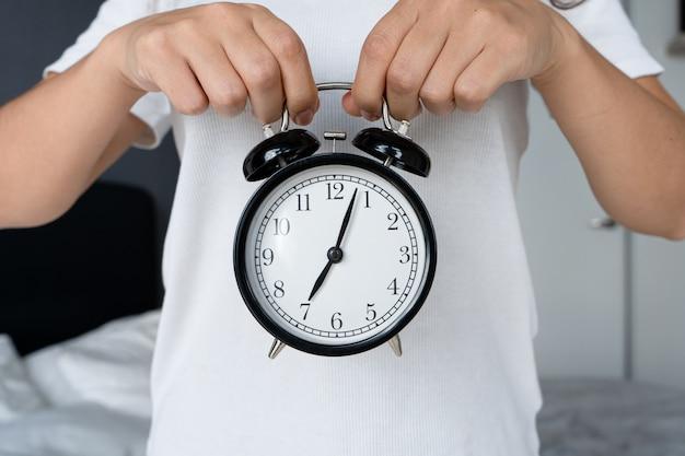 白いtシャツを着た男が、ベルの付いたスタイリッシュな黒の目覚まし時計を持っています。目覚まし時計で、八の始まり。起きる時間です。