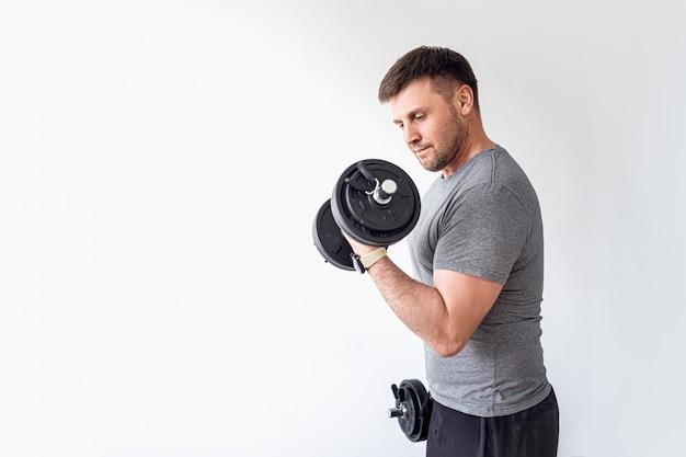 Tシャツとショートパンツの強力なアスレチックフィット男は自宅でダンベルでふくらはぎを上げる運動をやっています。