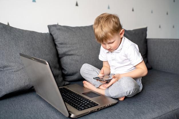 白いtシャツの子少年は灰色のソファーに座っているし、ラップトップで遊ぶ