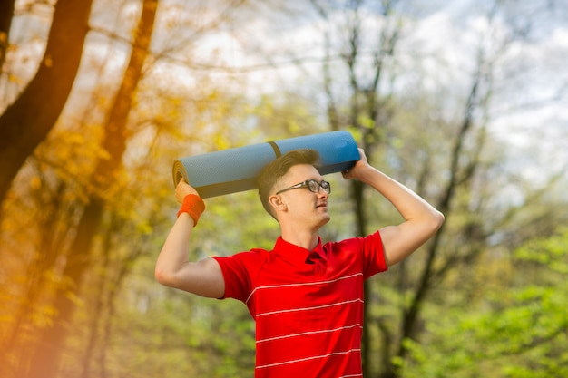 青いヨガマットと春の公園でポーズをとって赤いtシャツの若いスポーツ男。彼はヨガマットを頭にかざしています