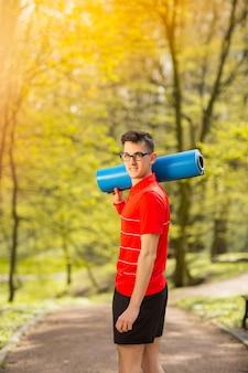公園のトラックの上に立って、青いヨガマットでポーズをとって赤いtシャツの若いスポーツ男。背景にぼやけた背景