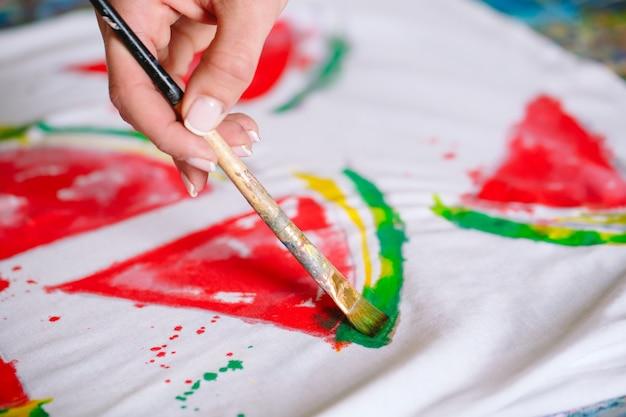 人は白いtシャツにスイカのスライスを描画します