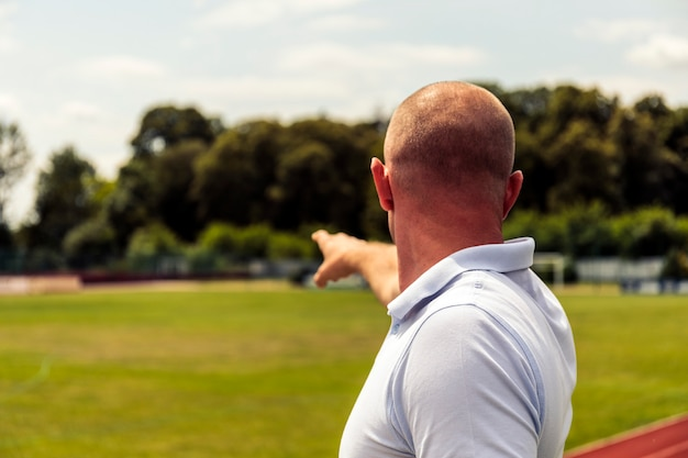 強いハゲ男はサッカー場で何かを指しています。 tシャツを指すでハンサムな男の背面図。